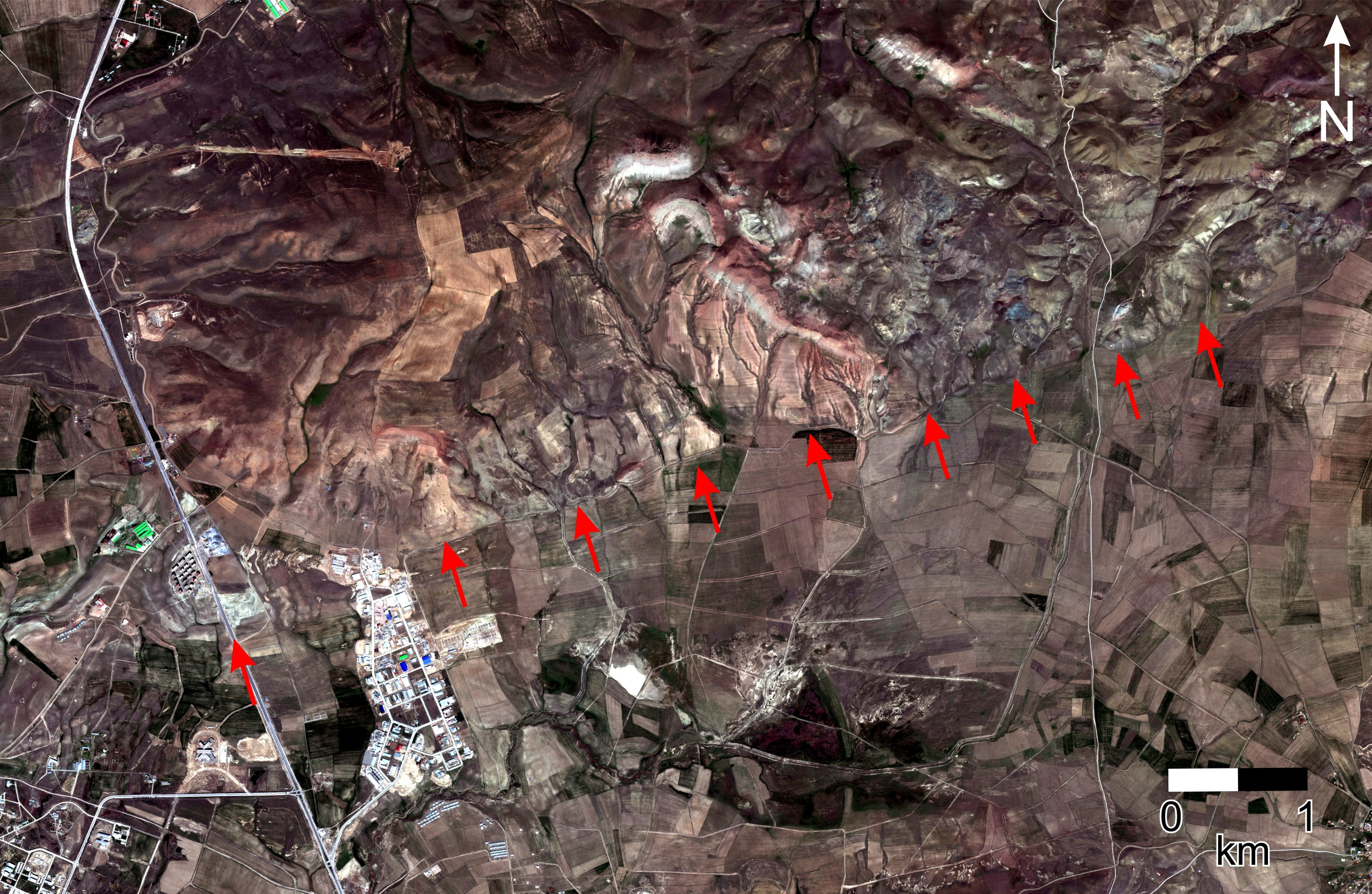 Figure 2: World-View 2 satellite imagery of the western fault segment, 10 km north of Van. The fault trace runs almost east-west (red arrows – the western most arrow is the location of figure 3). The surface geomorphology of the fault scarp is relatively clear in retrospect as there is a change in river incision moving from the south (flat agricultural fields) to the north across the fault (deeper stream and river valleys). This change in river cutting is due to the uplift of the hillside north of the fault from past earthquakes which push up the mountains. In the 2011 earthquake, the mountains to the north grew higher by almost 1 m.